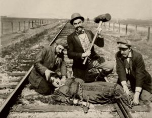 Ford Sterling with the sledgehammer and Mabel Normand tied in the rails in Barney Oldfield's Race for a Life (1913)